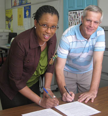 Mrs. Yolanda Bertin, St. Lucia National Commission for UNESCO and Mr. Remy Taupier, Secretary General of UPF-St. Lucia, sign a declaration of the International Day of Peace.