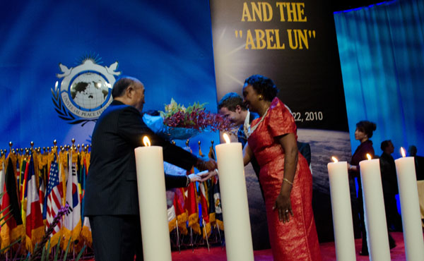 Mirriam Omala  from the African Union presents flowers to Rev. Dr. Moon at the conclusion of the evening.