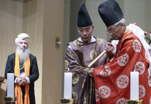 Two Shinto representatives lighting the peace candles