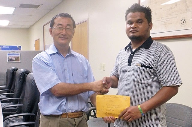 Rev. Kenichi Ito hands a donation to Mr. Patrick Langrine, Auditor General at the Ministry of Finance